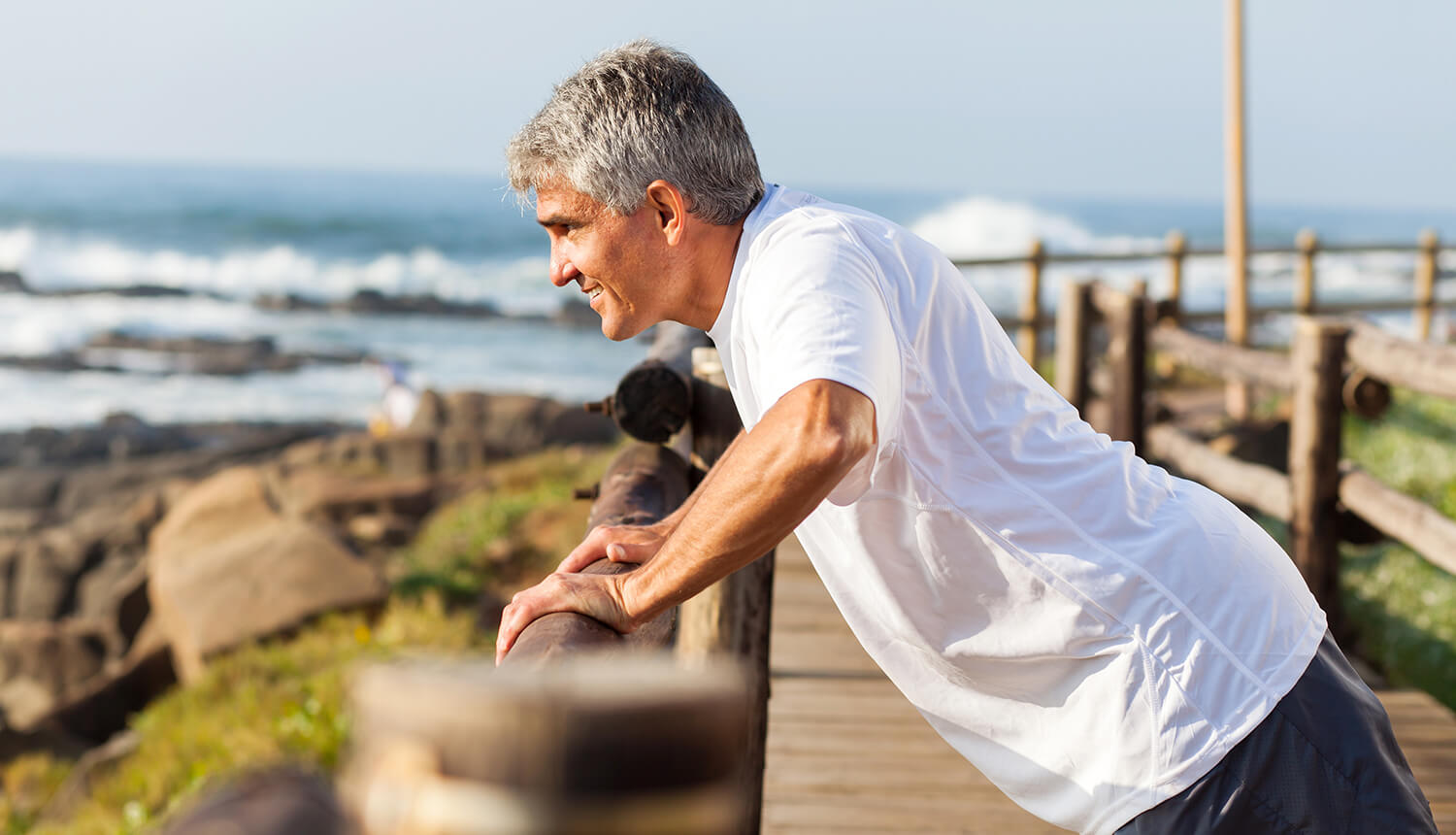 Man leaning over railing and stretching near the ocean