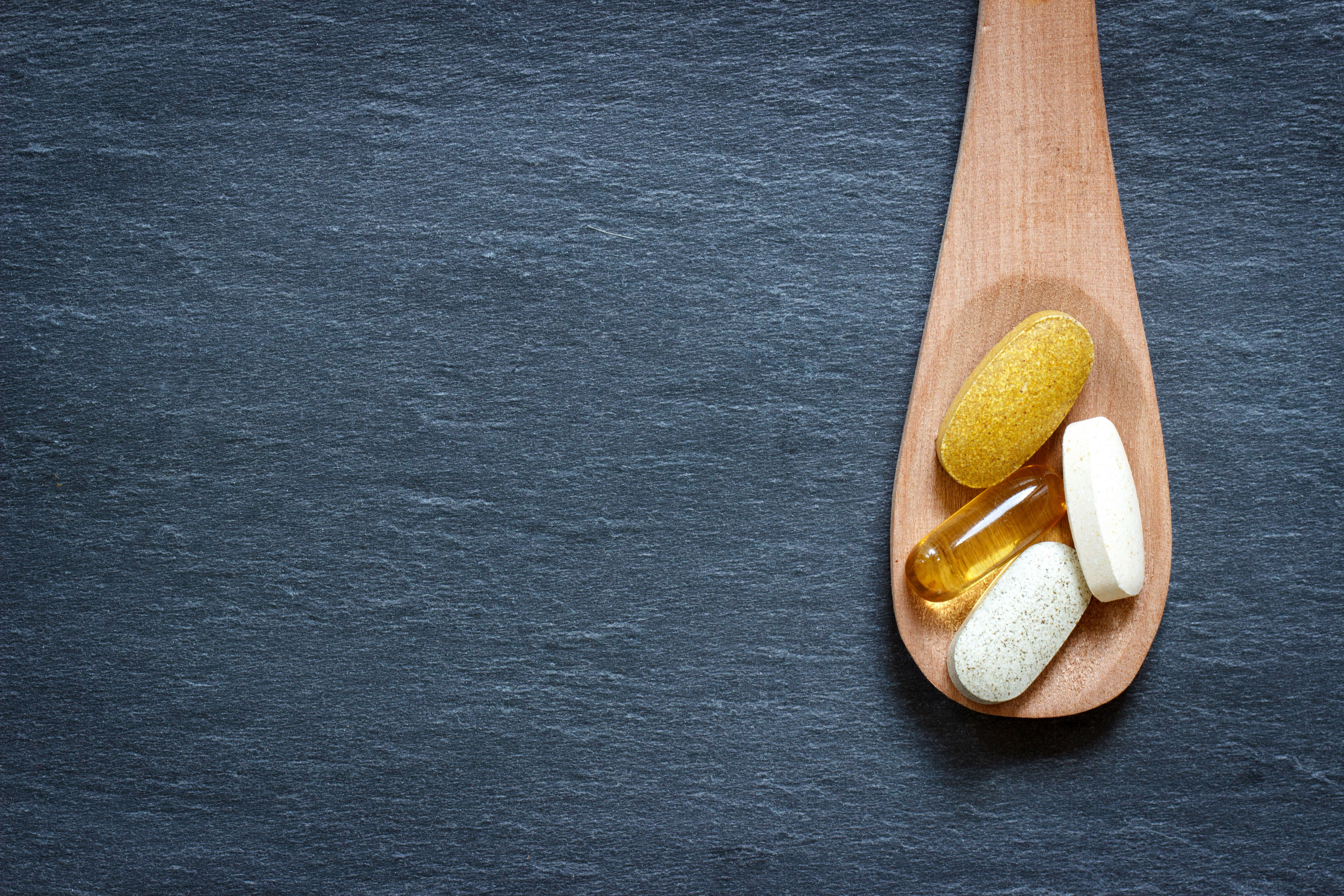 Healthy supplements on wooden spoon