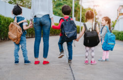 woman walking with kids to school
