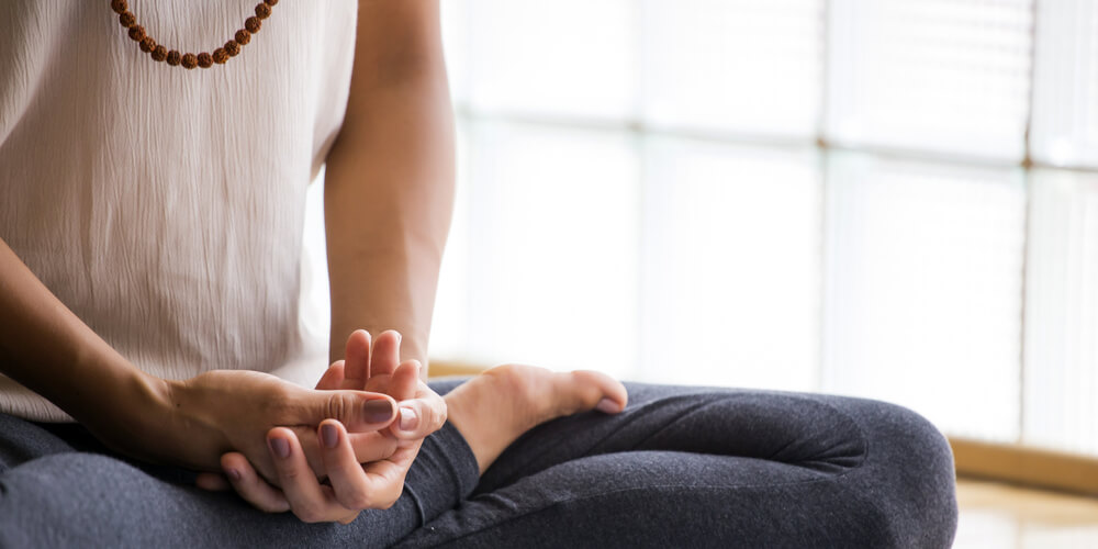 woman meditating in yoga studio with mala beads
